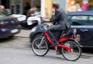 Un homme en costard au téléphone à vélo