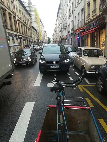 Une voiture arrive à contresens sur la voie cyclable