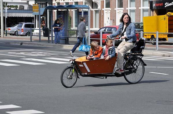 Une mère transporte ses deux enfants dans son vélo cargo