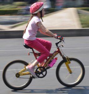 Fille sur un vélo enfant avec accessoires de sécurité
