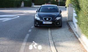 Un véhicule à l'arrêt sur la piste cyclable.