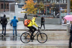 Un coursier à vélo effectuant sa livraison et qui pourra désormais profiter des avantages offerts par le syndicat des coursiers à vélo
