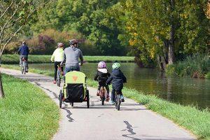 Famille à vélo avec remorque enfant le long du canal