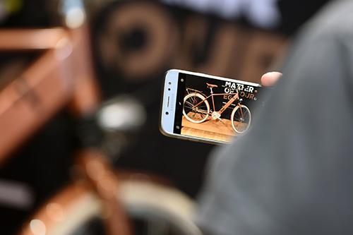 Un visiteur prend un vélo en photo avec son téléphone