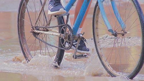 Cycliste roulant dans une flaque