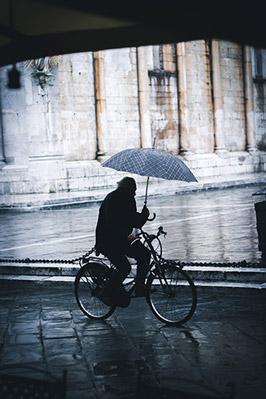 Pluie à vélo, cycliste avec un parapluie