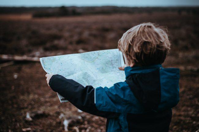 Enfant, en bivouac, tenant une carte